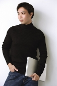 Man wearing black turtleneck, hand in pocket, holding laptop - Asia Images Group