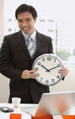 Businessman standing in front of desk, holding clock - Asia Images Group