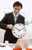 Businessman holding and pointing at clock - Asia Images Group