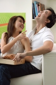 Couple at home in living room, sitting on sofa, laughing - Asia Images Group