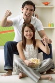 Couple in living room, man sitting on sofa, woman on floor - Asia Images Group