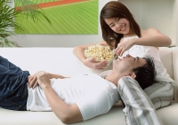 Couple at home, man lying on woman's lap, woman feeding man - Asia Images Group