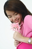 Woman dressed in pink, holding pink flower - Asia Images Group