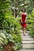 Woman walking along garden path, wearing red dress - Asia Images Group