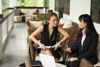Two businesswomen sitting on patio having a discussion - Asia Images Group