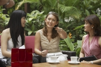 Three women at outdoor garden cafe, having a drink - Asia Images Group