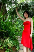 Woman wearing red dress, standing in garden - Asia Images Group