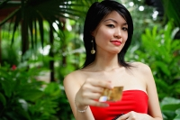 Woman in red dress, holding credit card - Asia Images Group