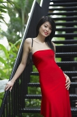 Woman in red dress, standing on stairs - Asia Images Group