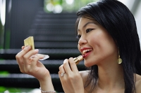 Woman applying make-up - Asia Images Group