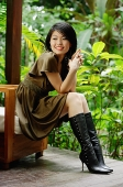 Woman sitting on chair, foliage behind her - Asia Images Group