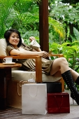 Woman sitting on chair in patio, shopping bags next to her, smiling at camera - Asia Images Group