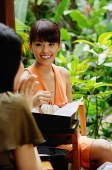 Two young women in outdoor cafe, one opening box - Asia Images Group