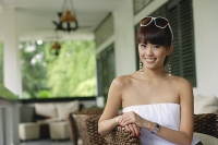 Young woman in white tube top, smiling at camera - Asia Images Group
