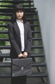 Businesswoman standing with briefcase - Asia Images Group