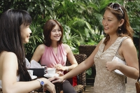 Three women talking at outdoor garden cafe - Asia Images Group