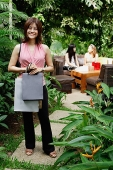 One woman standing on garden path, holding shopping bags - Asia Images Group