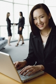 Portrait of businesswoman using laptop, smiling at camera - Asia Images Group