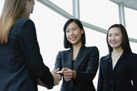 Three businesswomen exchanging business cards - Asia Images Group