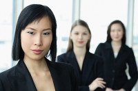 Businesswoman looking at camera, other women behind her - Asia Images Group