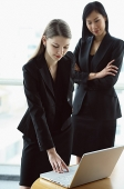 Two women standing in front of laptop - Asia Images Group