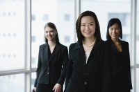 Businesswomen in a row, smiling at camera - Asia Images Group
