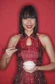 Woman against red background, dressed in cheongsam, holding bowl of rice - Asia Images Group