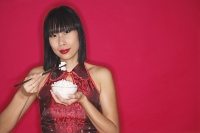 Woman in cheongsam holding bowl of rice - Asia Images Group