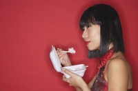 Woman against red background, eating rice from a Styrofoam container - Asia Images Group