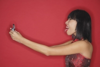 Woman holding mobile phone, sticking tongue out - Asia Images Group