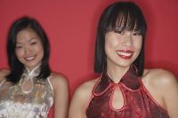 Two women, red background, looking at camera - Asia Images Group