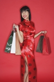 Woman in red cheongsam, against red wall, carrying shopping bags - Asia Images Group