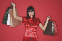 Woman in red cheongsam, carrying shopping bags, smiling at camera - Asia Images Group