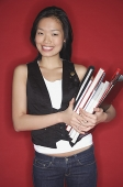 Woman carrying books, smiling at camera - Asia Images Group
