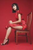 Woman in cheongsam, sitting on chair - Asia Images Group