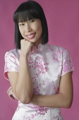 Woman in pink cheongsam, hand on chin, smiling - Asia Images Group
