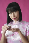 Woman in pink cheongsam, holding Chinese tea cup - Asia Images Group