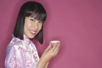 Woman holding Chinese tea cup - Asia Images Group