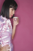 Woman drinking Chinese tea, hand on hip - Asia Images Group