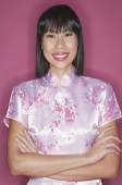 Woman in pink cheongsam, arms crossed, smiling - Asia Images Group