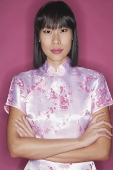 Woman in pink cheongsam, arms crossed - Asia Images Group