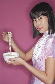 Woman holding bowl of noodles and chopsticks - Asia Images Group