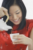Woman pouring tea - Asia Images Group
