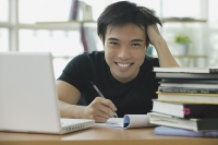Young adult  with laptop and books, smiling at camera - Asia Images Group