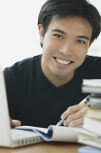 Young adult smiling at camera, laptop and books next to him - Asia Images Group