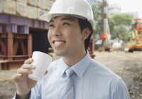 Businessman wearing hardhat, drinking from disposable cup - Asia Images Group