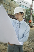 Businessman wearing hardhat, looking at blueprints - Asia Images Group