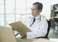 Doctor in office, looking at folder - Asia Images Group