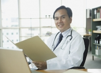 Doctor sitting in office, smiling at camera - Asia Images Group