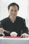 Man with bowl of rice and chopsticks, smiling at camera - Asia Images Group